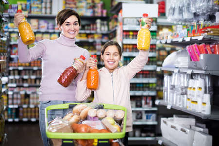 cheerful mother with daughter choosing refreshing beverages in supermarket