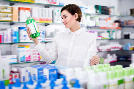 Happy woman customer browsing rows of drugs