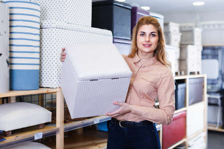 Adult saleswoman offering soft pouf in store
