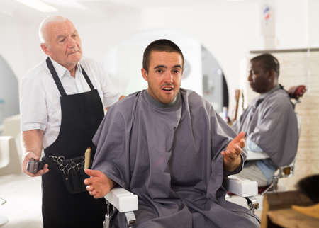 Shocked client with confused aged hairdresser