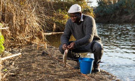 Fisherman putting fish in bucket