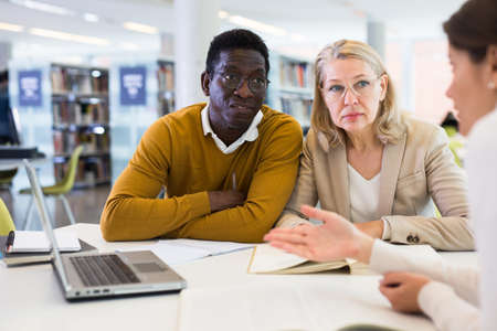 Students sitting in library, working with professor