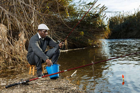Man fishing with rods on river