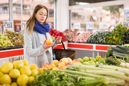 Woman is choosing fresh apples in grocery store