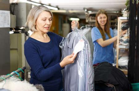 Woman holding her clean clothes Foto de archivo