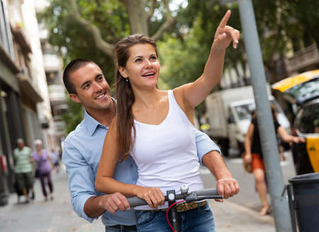 Man and woman enjoying electro scooter riding
