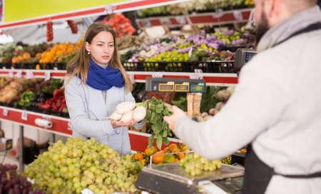 Seller assisting customer to weigh radish