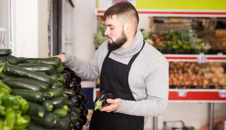 Male shop assistant lays fresh cucumber on counter in grocery shop