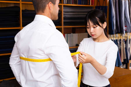Chinese woman tailor using measurement tape with client in mens cloths store