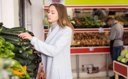 Female shopper picks cucumbers at grocery store
