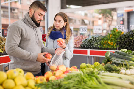 Friendly couple examining apples in grocery shop Archivio Fotografico