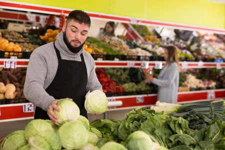 Male shop assistant lays fresh cabbage on counter in grocery shop Stok Fotoğraf