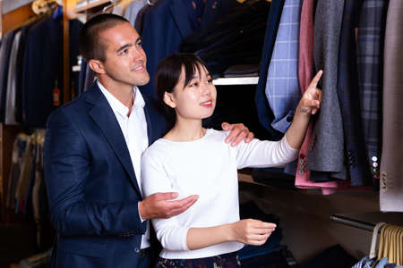 Smiling couple examining various suits in mens cloths store