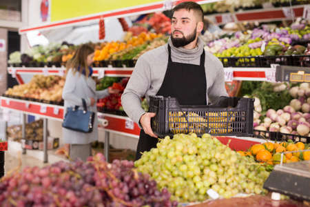 Man seller moving box of bananas in grocery shop