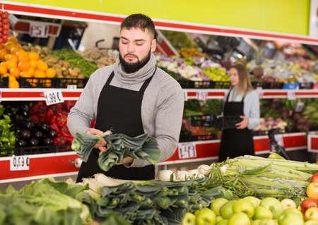 Male shop assistant in apron lays fresh leek in supermarket