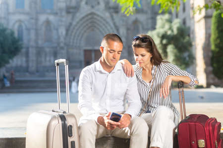 Couple of travelers sitting on bench, booking accommodations with phone