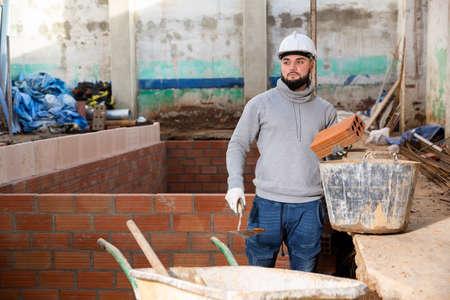 Bricklayer installing brick wall