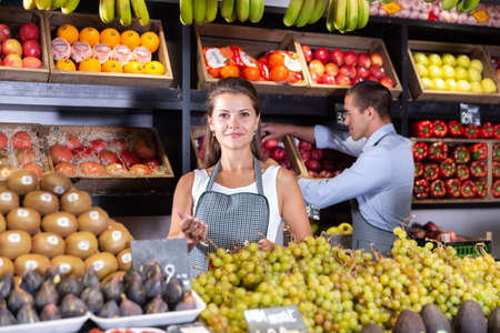 female seller offers fruits and vegetables