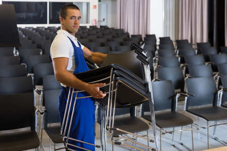 Worker carrying chairs in empty room Reklamní fotografie