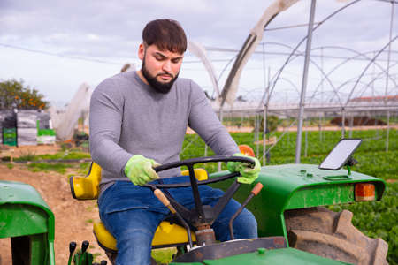 Confident farmer working on tractor in greenhouse