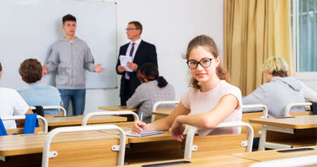 Young girl is sitting at the desk in classroom