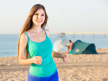 Female in blue T-shirt is jogging