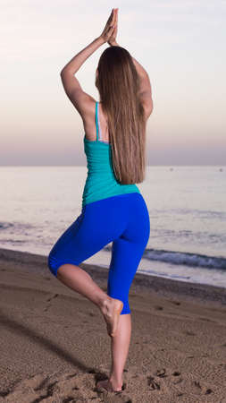Portrait of sportswoman which is standing and practicing asana 스톡 콘텐츠