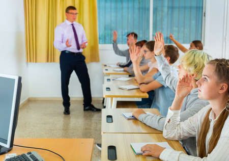 Teenage students raising hands to answer during lesson