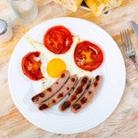 Fried eggs with sausage and tomatoes