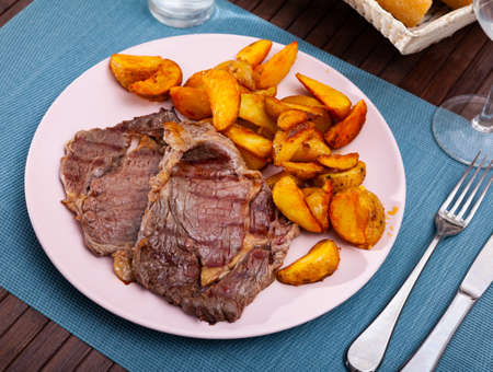 Delicious grilled beef with baked potatoes at plate