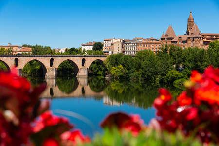 Medieval bridge over the Tarn river in Montauban city on sunny day