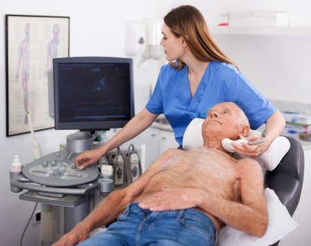 Female technician diagnosing male patient using modern ultrasound scanner in private clinic Archivio Fotografico
