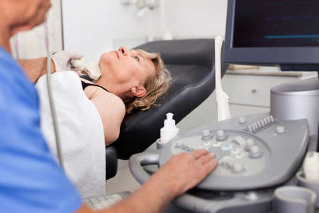 Elderly man sonographer using ultrasonography machine checking female patient in hospital diagnostic room