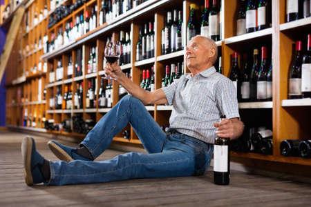 Portrait of senior man sitting on floor in winery tasting room, drinking red wine