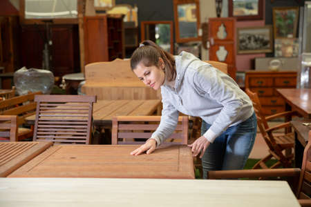 Woman choosing new furniture in salon