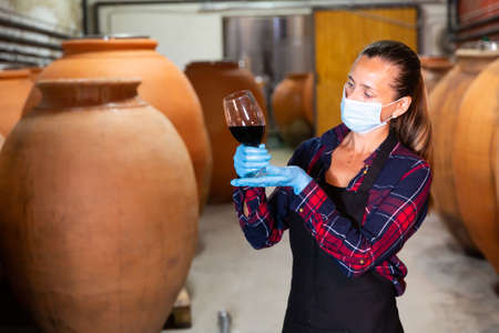 Female wine worker in a protective mask checking quality of product