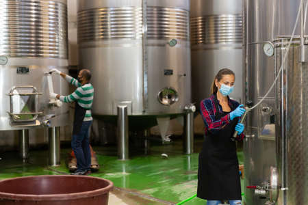 Female worker in mask working at winery