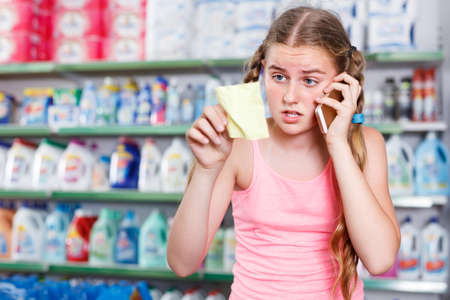 concentrated girl standing in store choosing products while talking by phone and looking at shopping list