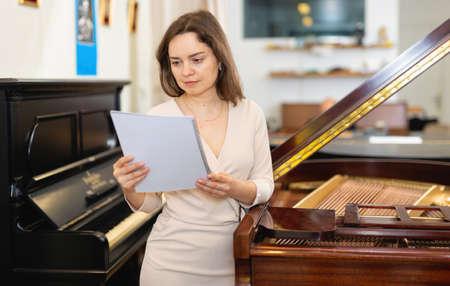 Pretty saleswoman in piano record store