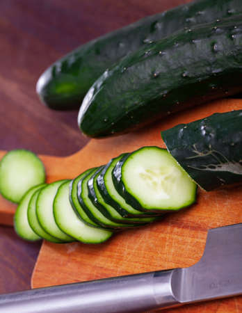 Chopped cucumbers on wooden background