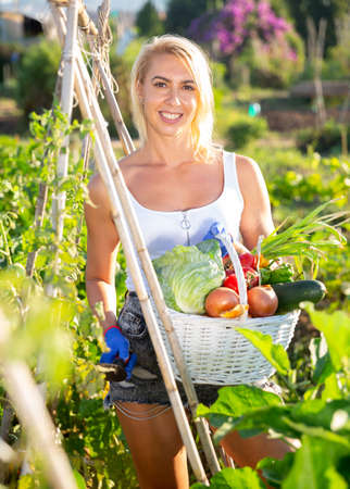 Woman posing in garden with picked vegetables