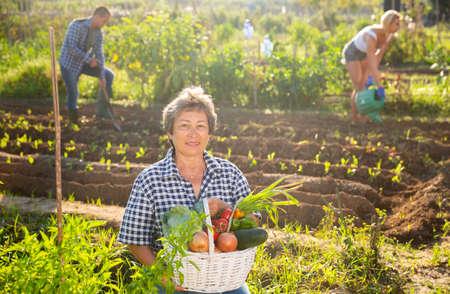Mature female gardener posing with harvested vegetables