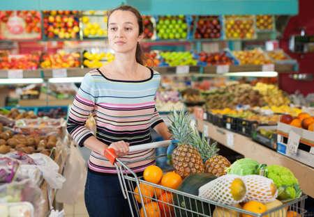Positive Caucasian female choosing fresh fruits at shop