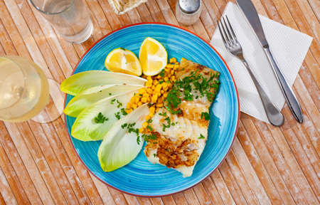 Delicious fried cod fillet with endive, corn, and greens Imagens