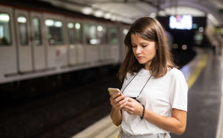 Female using mobile phone on station
