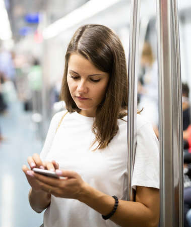 Woman holding smartphone in subway car