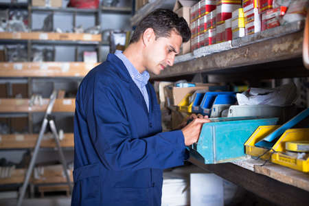 Salesman is checking small details in boxes