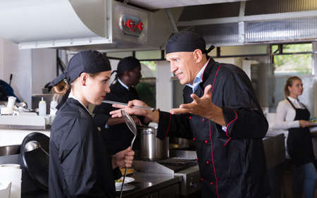 Chef dissatisfied with work of girl Stock fotó