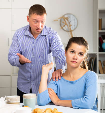 Irritated young spouses quarrelling in home kitchen interior Stock Photo