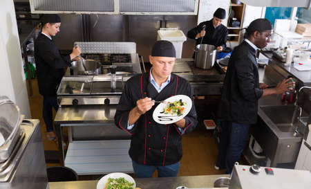 Staff of restaurant with chef working